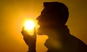 man pretending to eat sun