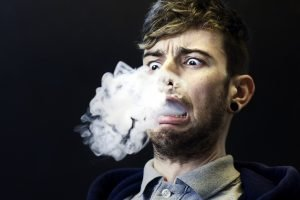 man exhaling vape