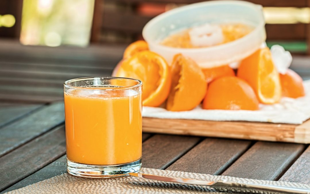 glass of orange juice with squeezed oranges and juicer in background