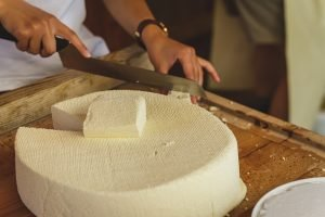 wheel of raw cheese being sliced