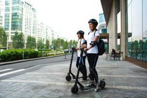 two women on scooters wearing helmets