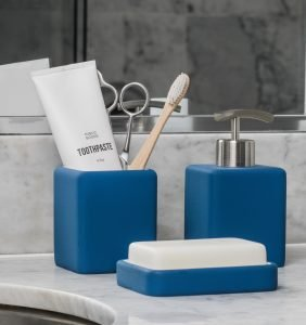 toothbrush and toothpaste in blue cup on bathroom counter