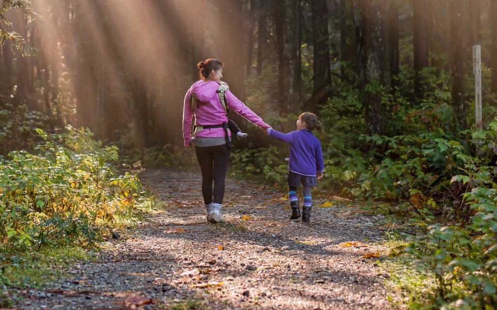 mother and daughter taking a walk in the woods