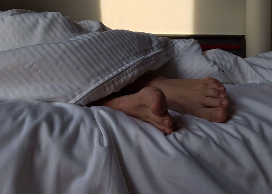feet sticking out from under bed covers