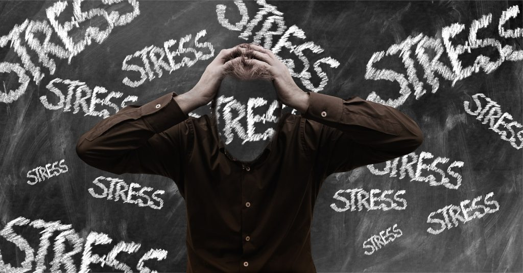 man with hands on head surrounded by the word stress