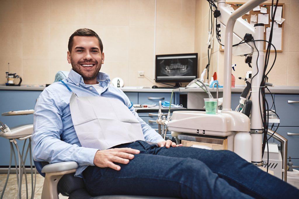 cheerful man in dental chair